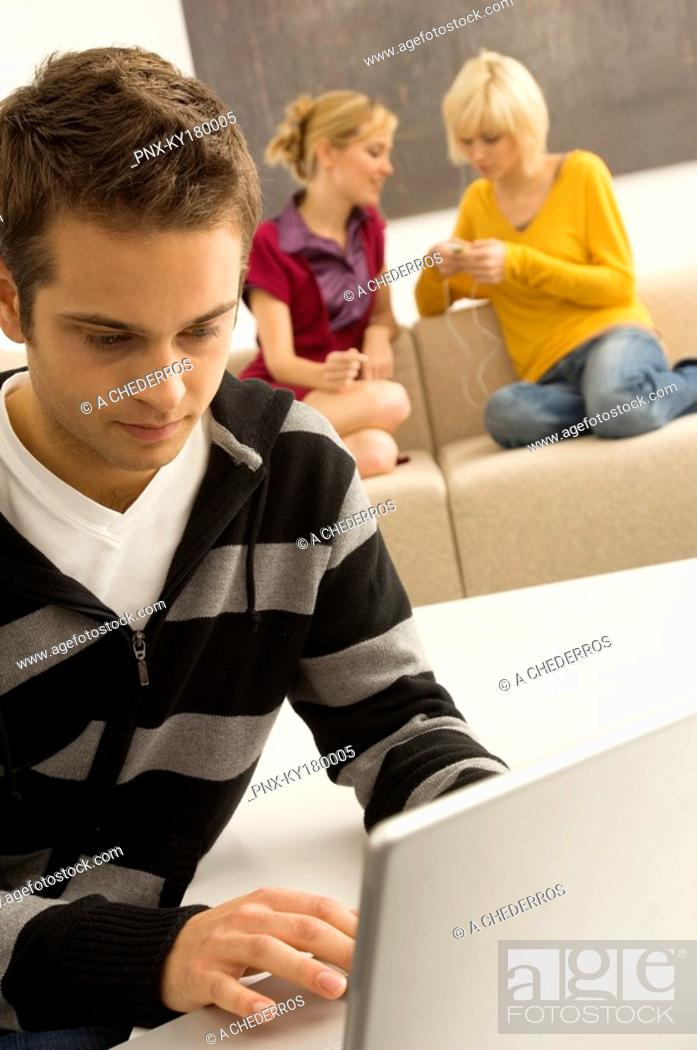 Stock Photo: Young man using a laptop with two young women listening to an MP3 player in the background.