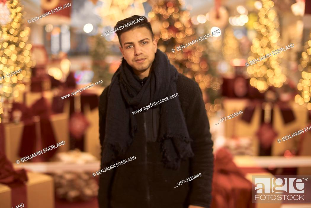 Stock Photo: young man, Afghan ethnicity, in front of christmas decoration, in Munich, Germany.