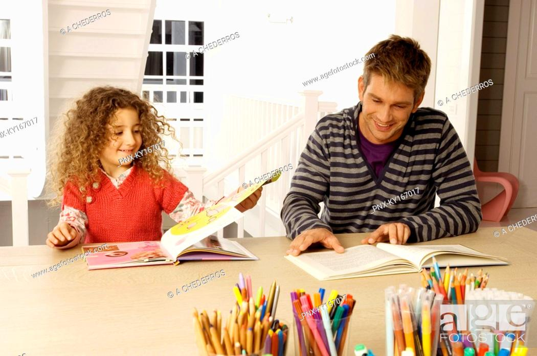 Stock Photo: Mid adult man sitting with his daughter and reading books.