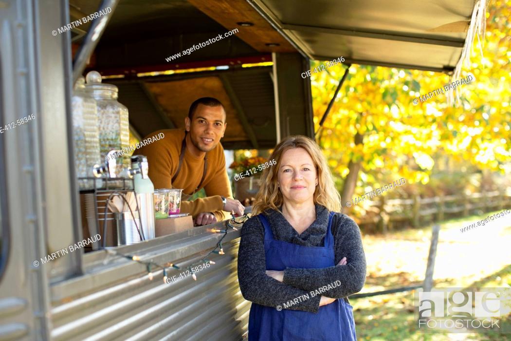 Photo de stock: Portrait confident food cart owners in autumn park.