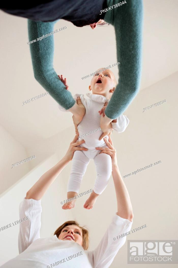 Stock Photo: Woman giving her baby to another woman.