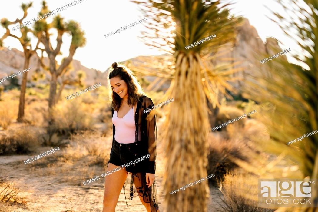 Stock Photo: USA, California, Los Angeles, smiling woman walking in Joshua Tree National Park.