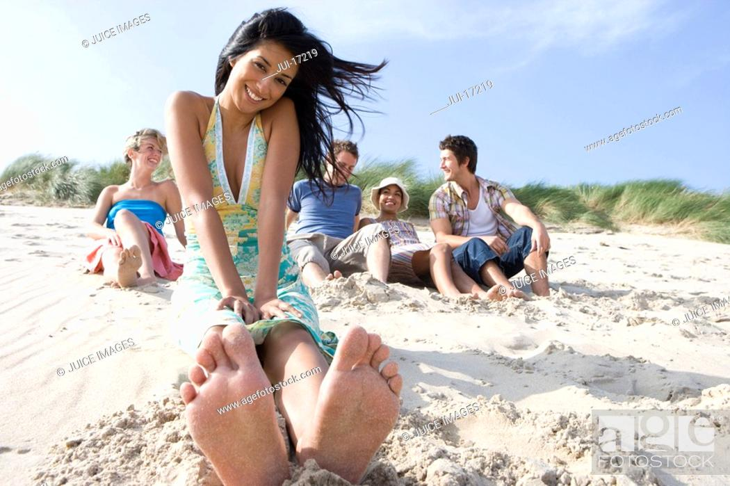 Stock Photo: Portrait of young Asian woman sitting at beach, friends in background.