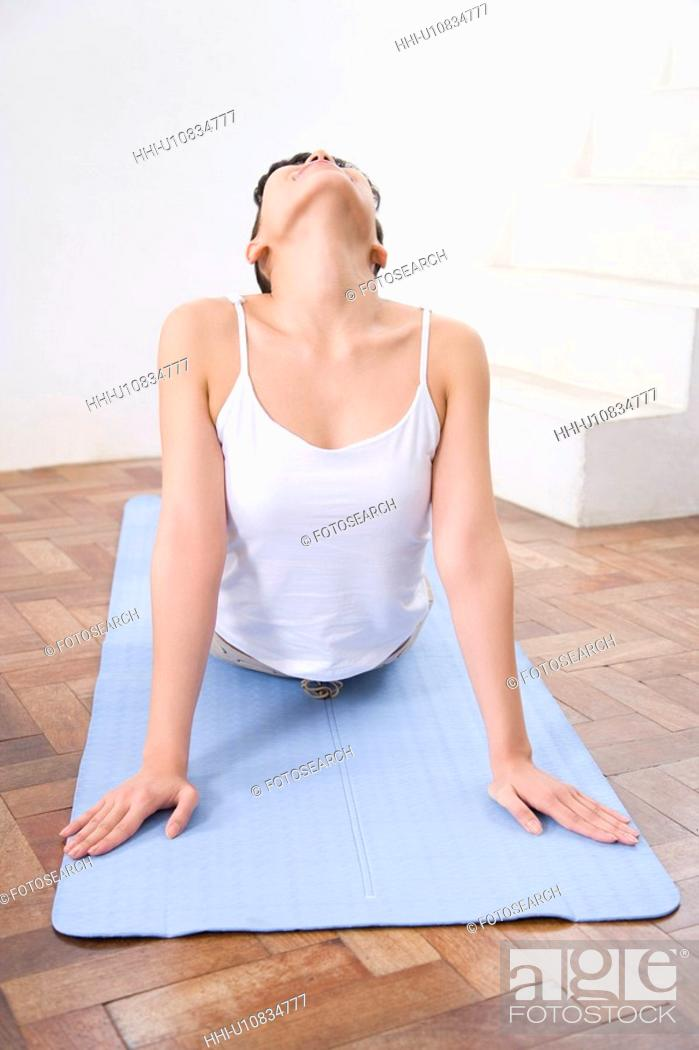 Stock Photo: Young woman doing yoga exercise, stretching, front view.