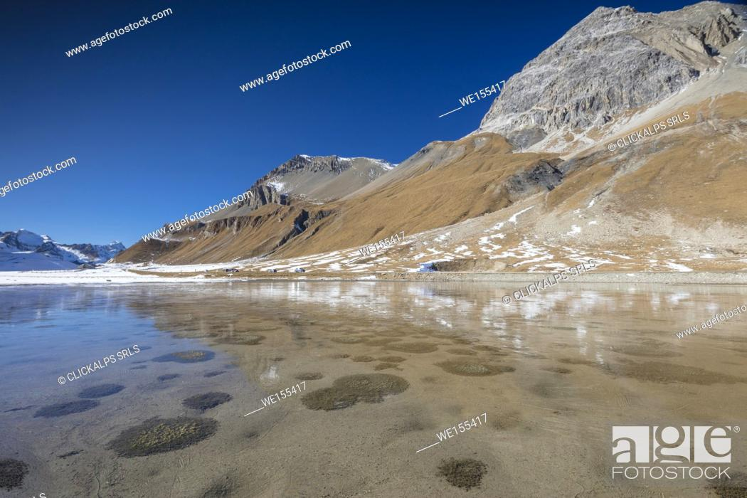 Stock Photo: The blue sky frames the rocky peaks reflected in the alpine lake Julier Pass canton of Graubünden Engadine Switzerland Europe.