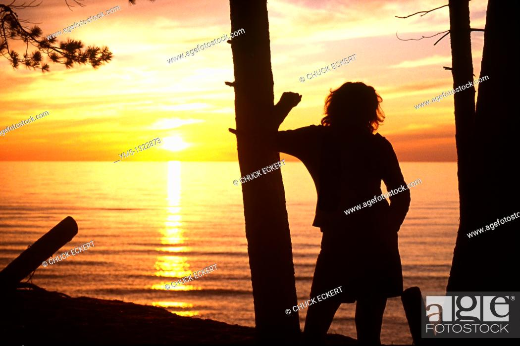 Stock Photo: Woman leaning on pine tree while watching sunset over Lake Superior.