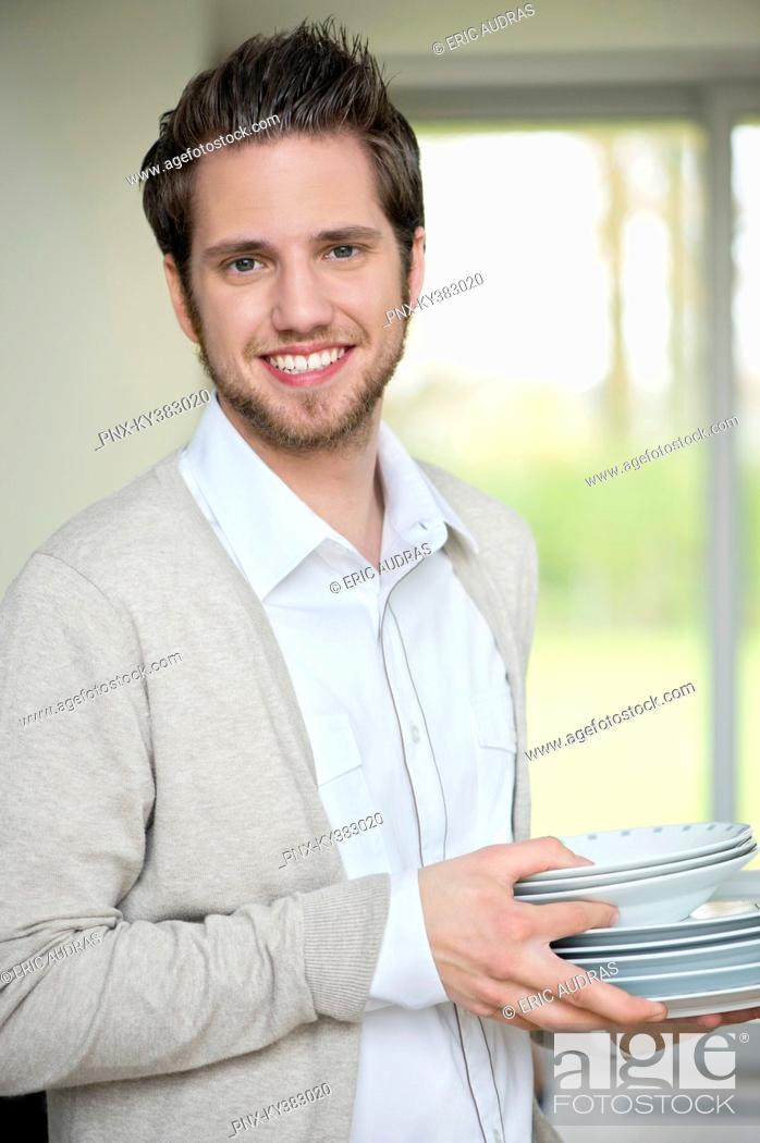 Stock Photo: Portrait of a man carrying plates.