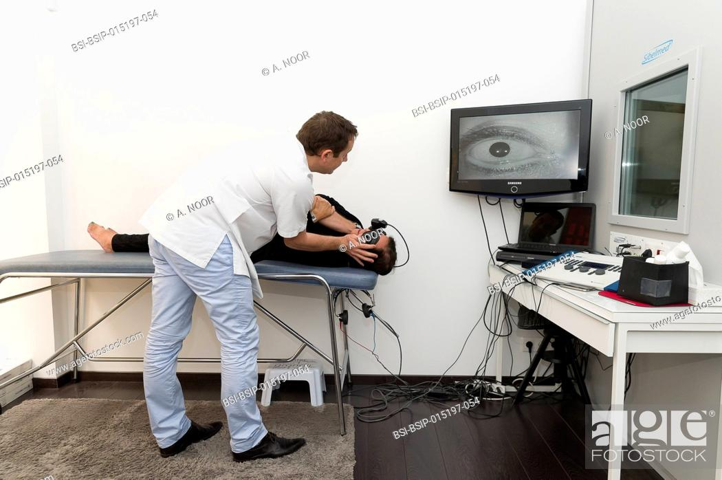Stock Photo: Reportage on an ENT doctor in Nice, France, treating patients suffering from dizziness. Treating benign paroxysmal positional vertigo (BPPV) manually in an.