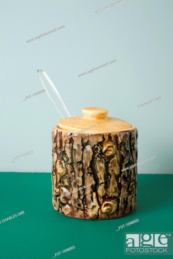 Stock Photo: A ceramic honey jar made to look like tree bark.