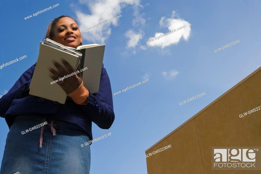 Stock Photo: Low angle view of a young woman reading a textbook.
