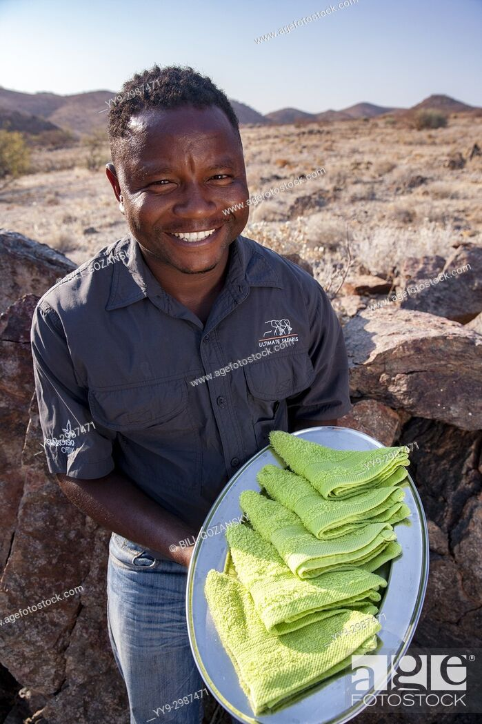 Photo de stock: Staff person with refreshing welcome towels - Huab Under Canvas, Damaraland, Namibia, Africa.