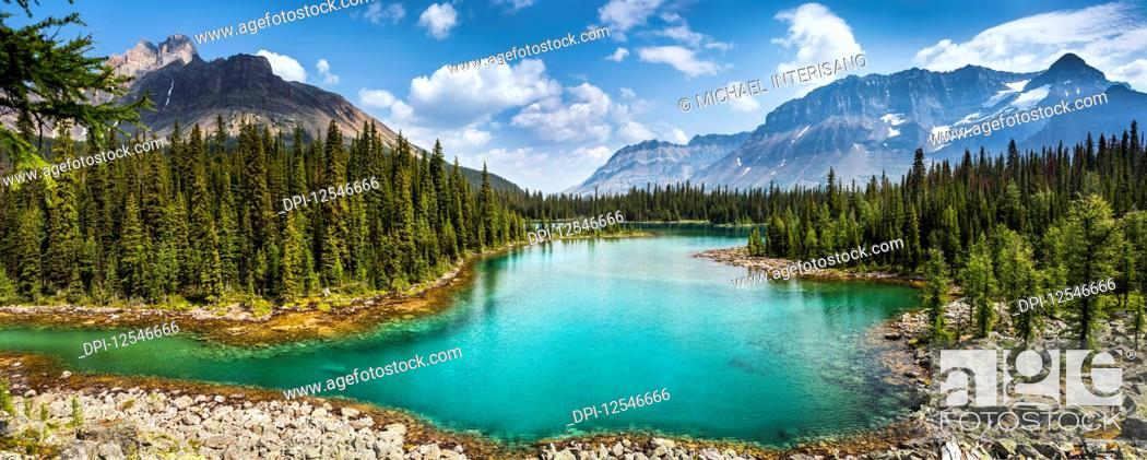 Stock Photo: Colourful alpine lake with mountains, blue sky and clouds in the background; British Columbia, Canada.