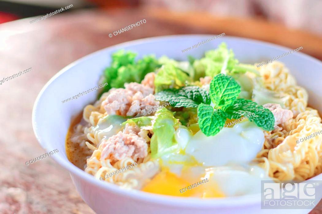 Stock Photo: Chinese noodles with minced pork and egg in bowl on wooden table.