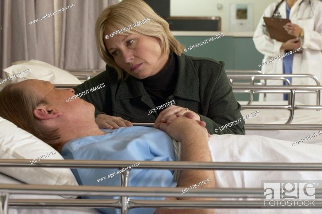 Stock Photo: Wife consoling husband in hospital.