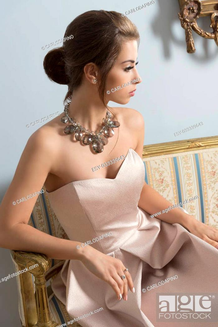 Stock Photo: indoor portrait of aristocratic brunette girl sitting on vintage sofa with elegant pink dress, shiny necklace and classic hair-style.