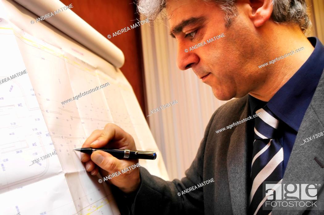 Stock Photo: Male architect working in progress on blueprints.