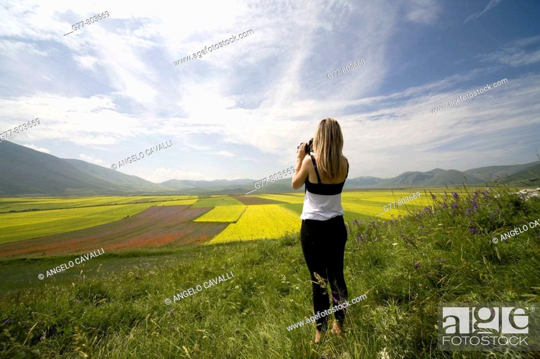 Stock Photo: Italy, Umbria, Norcia, Highland of Castelluccio di Norcia. Woman taking pictures of Lentils Fields.