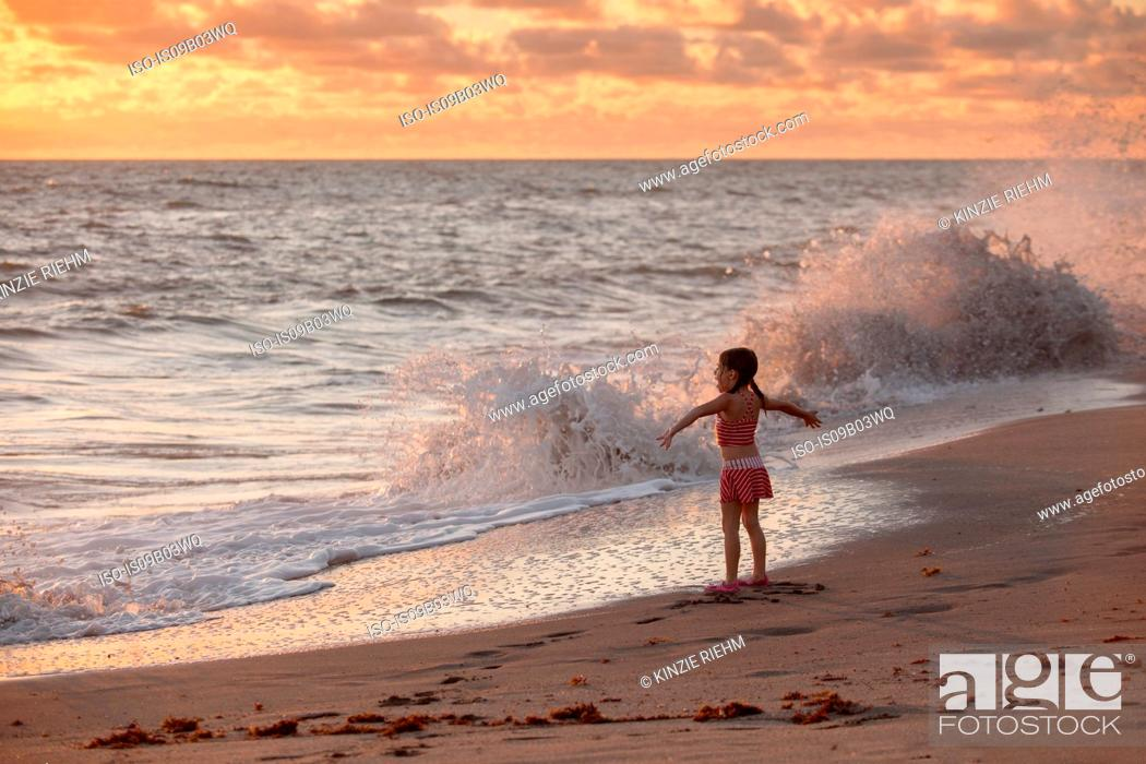 Stock Photo: Girl with arms open whilst waves splash at sunrise, Blowing Rocks Preserve, Jupiter Island, Florida, USA.