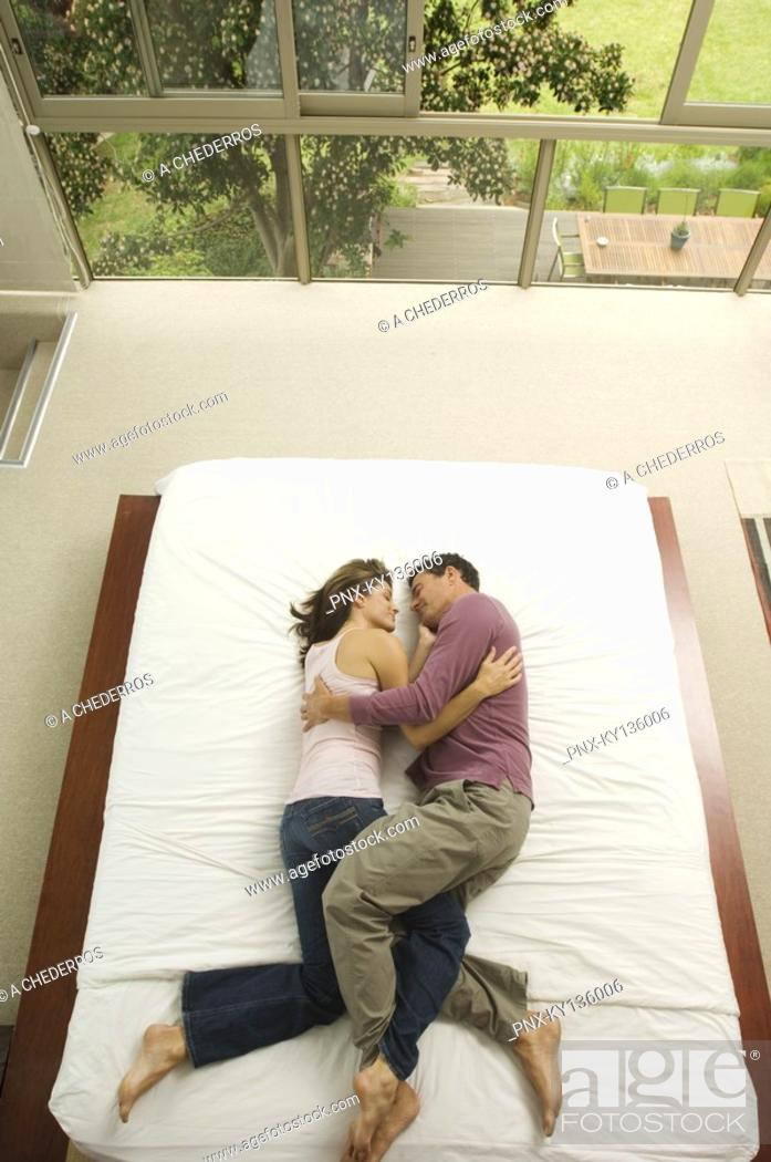 Stock Photo: Couple sleeping in a bed, view from above, indoors.