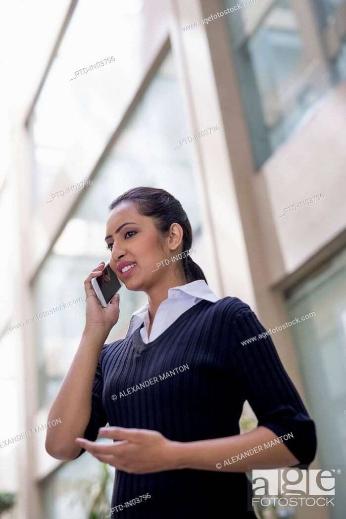 Stock Photo: India, Businesswoman talking on mobile phone outside office building.