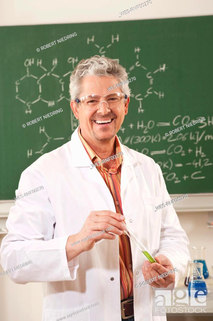 Stock Photo: Germany, Emmering, Senior man holding test tube, smiling, portrait.