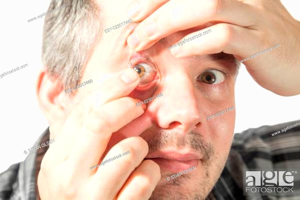 Stock Photo: putting on a contact lens.