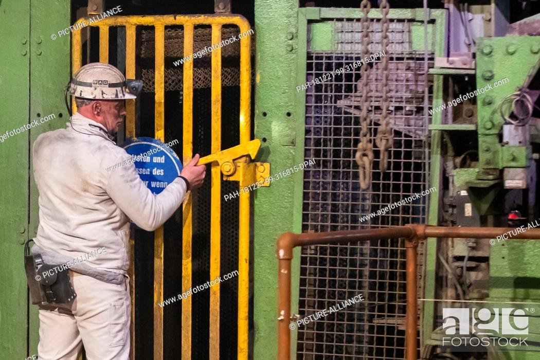 Stock Photo: 21 December 2018, North Rhine-Westphalia, Bottrop: A buddy pushes the bar at the entrance of the winding shaft. With the symbolic extraction of the last piece.