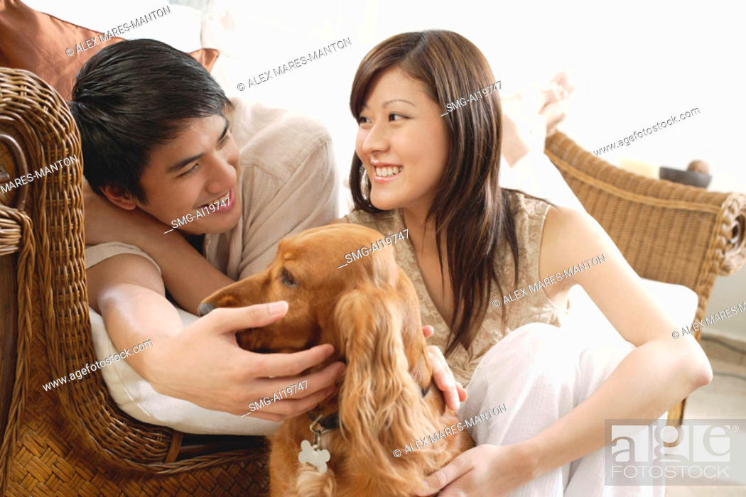 Stock Photo: Couple at home with Cocker Spaniel dog.