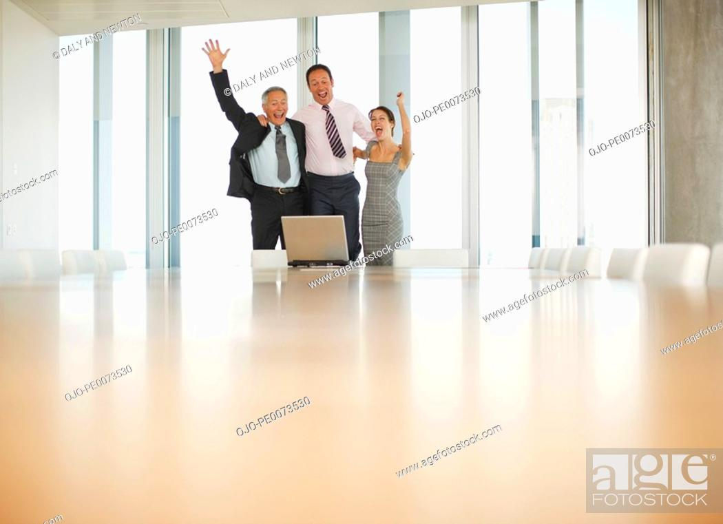 Stock Photo: Excited business people celebrating in front of laptop in conference room.