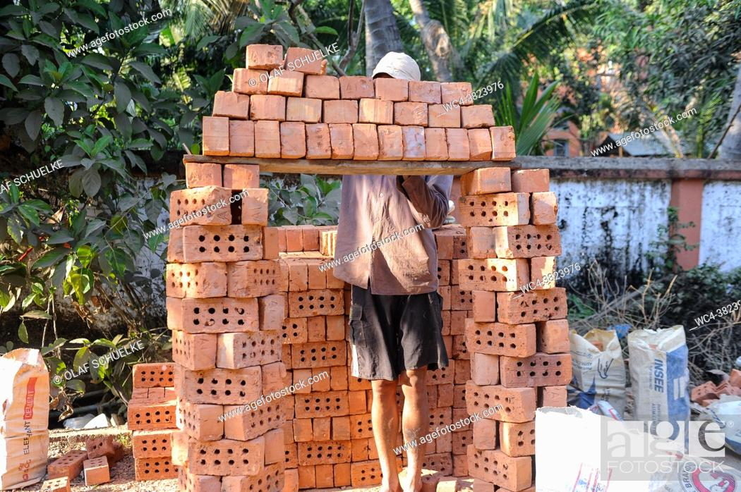 Stock Photo: Yangon, Myanmar, Asia - A construction worker piles up bricks onto a wooden board for transport to a nearby building site.