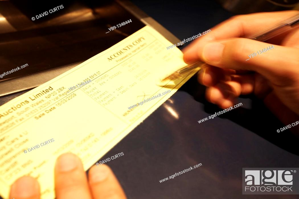 Stock Photo: Close up of a man signing a cheque.