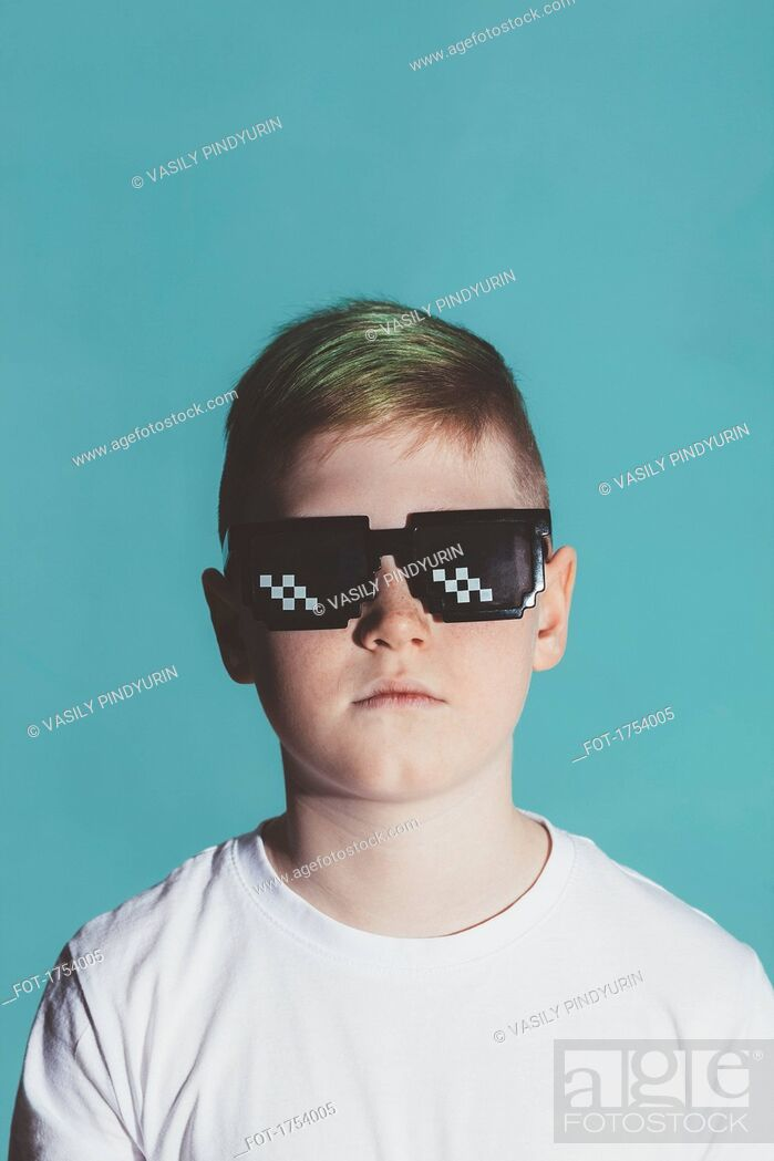 Stock Photo: Boy wearing sunglasses against blue background.