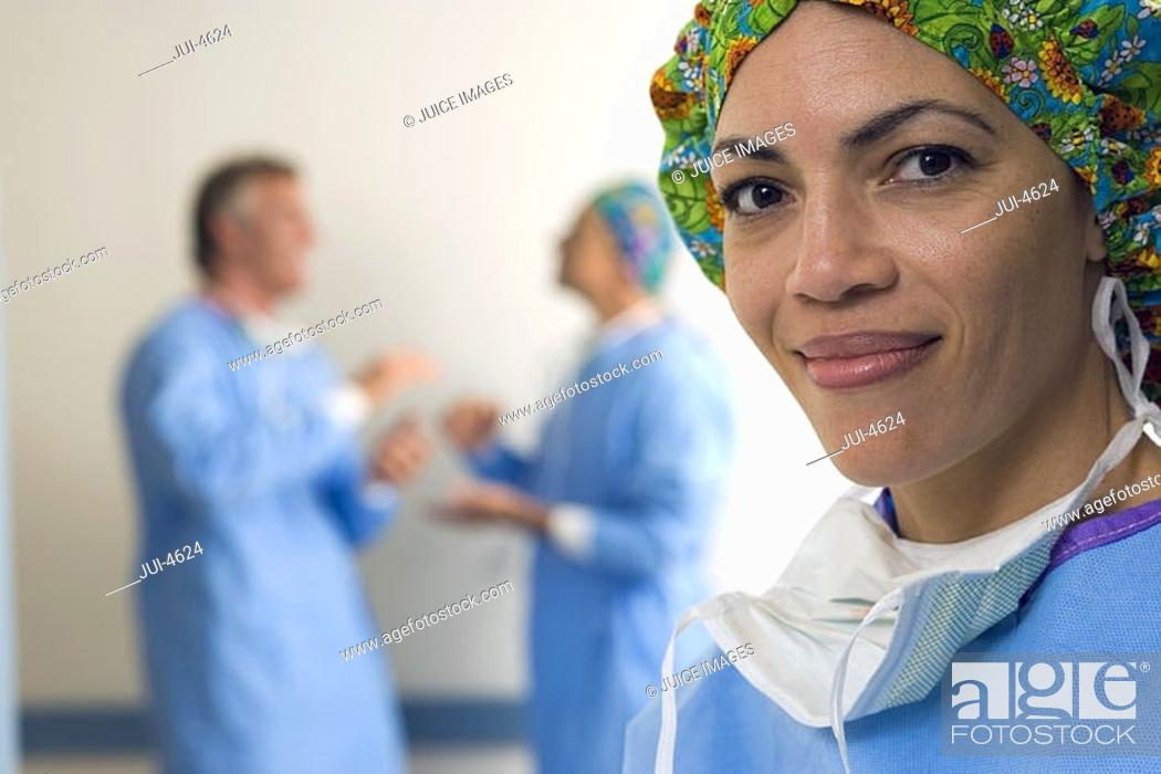 Stock Photo: Surgeons talking in hospital corridor, focus on female surgeon in foreground, smiling, portrait.