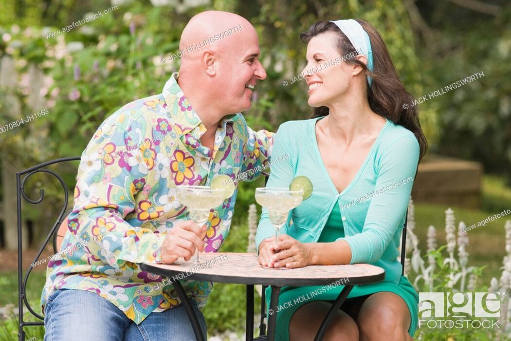 Stock Photo: Close-up of a mature couple sitting at a table and holding martini glasses.