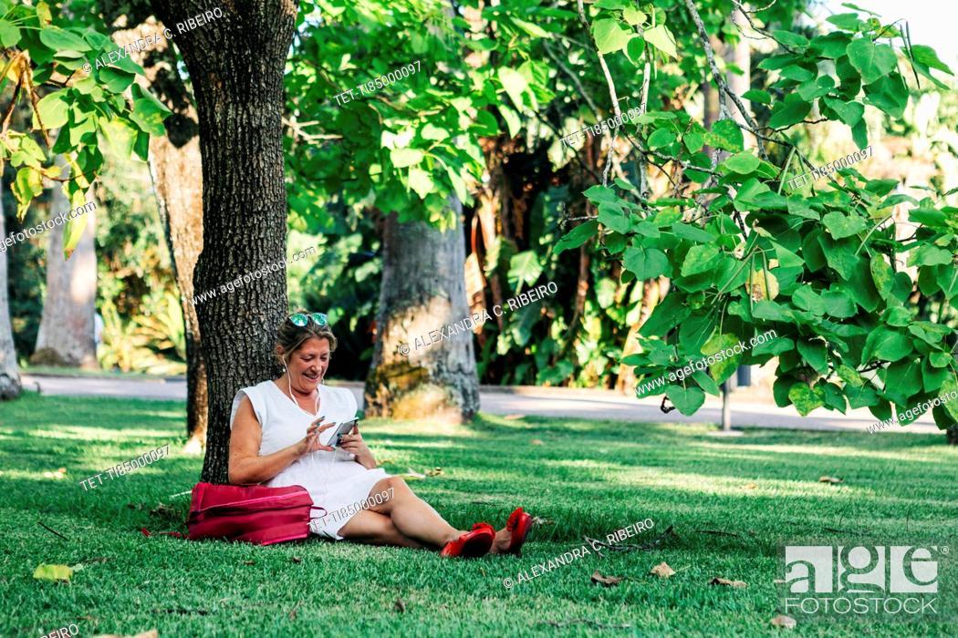 Photo de stock: Woman using smart phone under tree.