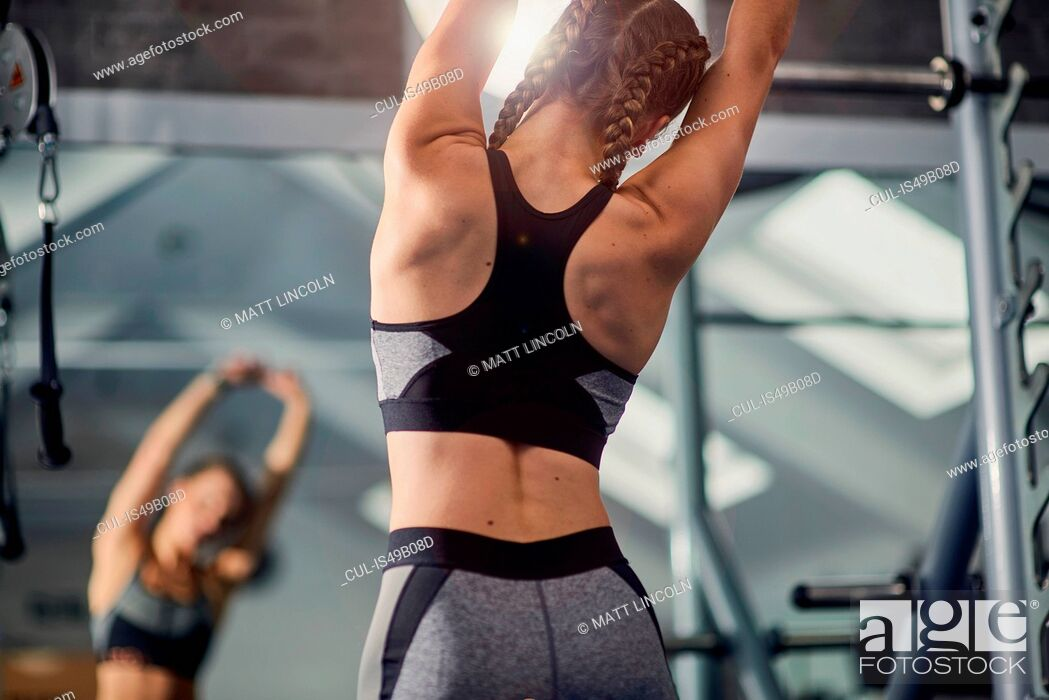 Stock Photo: Young woman training, looking in mirror while stretching arms in gym.
