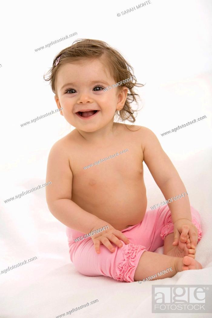 Stock Photo: Baby girl sitting on baby blanket, smiling, portrait.