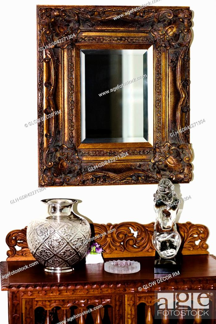 Stock Photo: Showpieces On A Chest With Mirror In A Living Room.