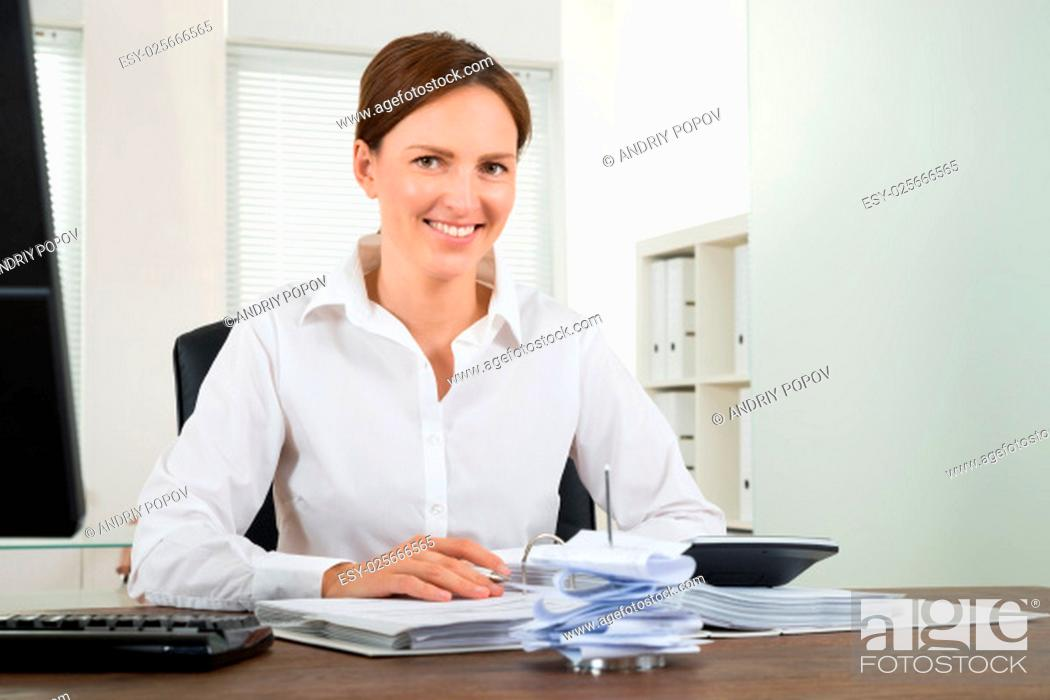Stock Photo: Happy Businesswoman Calculating Bills With Calculator At Desk.