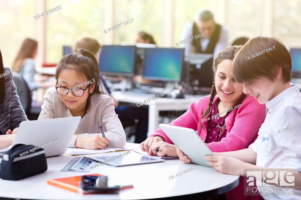 Stock Photo: Students using digital tablet and laptop in library.