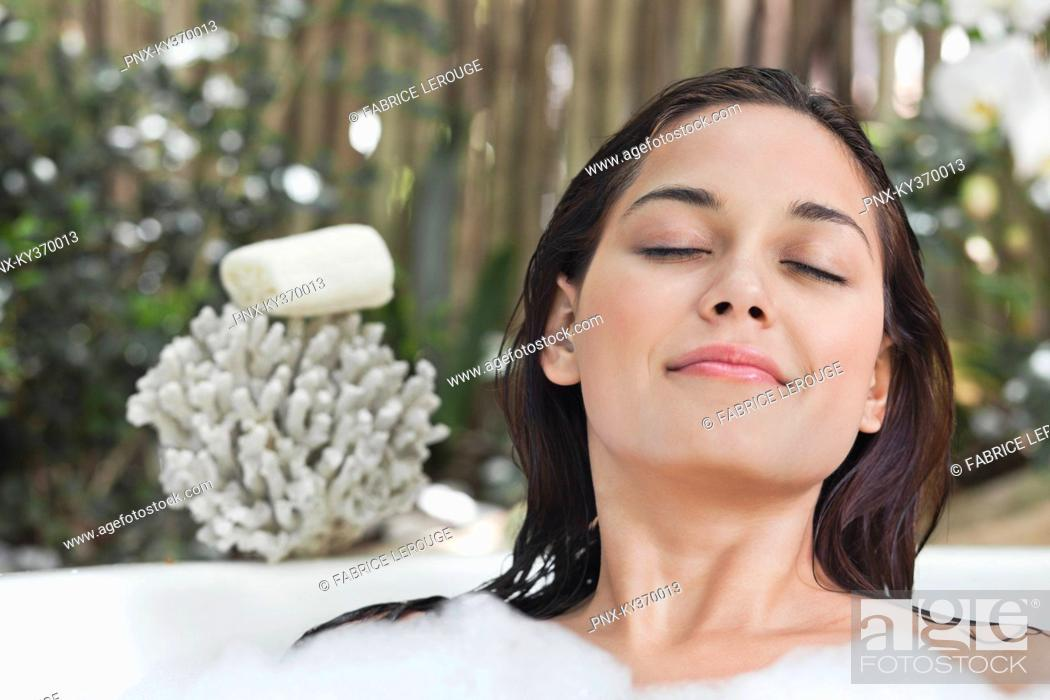 Stock Photo: Beautiful young woman taking bubble bath with her eyes closed.