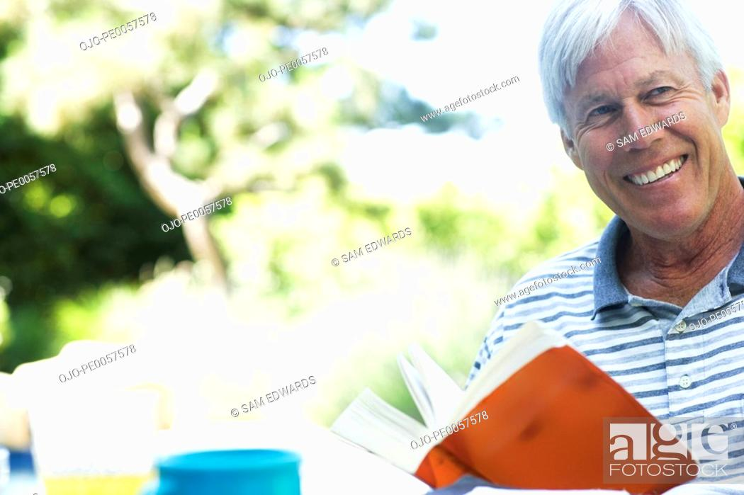 Stock Photo: Man with book outdoors smiling.