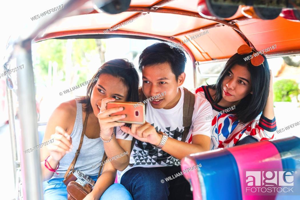 Stock Photo: Thailand, Bangkok, three friends riding tuk tuk taking pictures with smartphone.