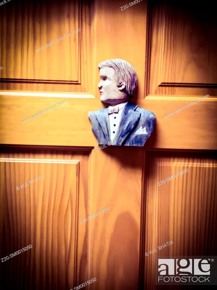 Stock Photo: A wood sculpture of a well dressed man on a Men's toilet door, Quebec, Canada.