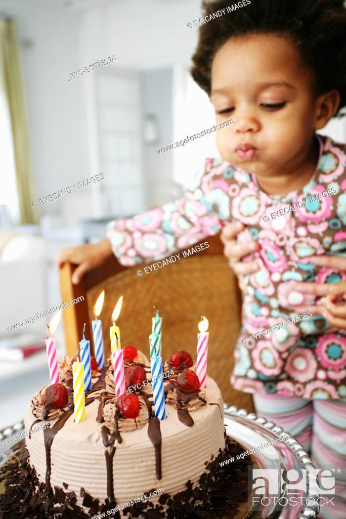 Stock Photo: African American child blowing out birthday candles.