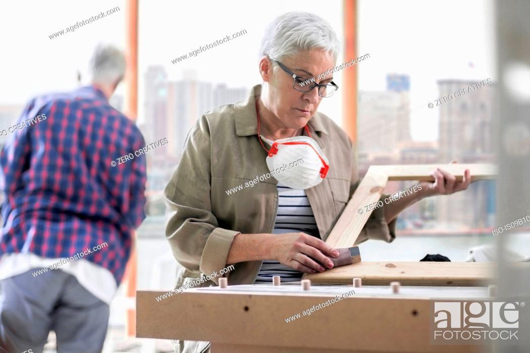Stock Photo: Mature female carpenter sanding picture frame in furniture making workshop.