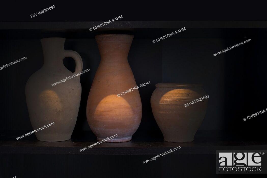 Stock Photo: Three terracotta vases earthenware household item handmade on a dark shelf isolated on black.