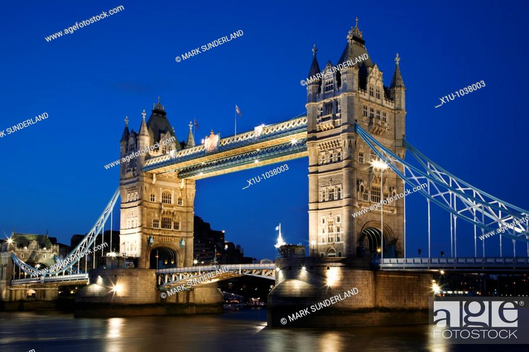 Stock Photo: Reflections of the Floodlit Tower Bridge in the River Thames at Dusk London England.