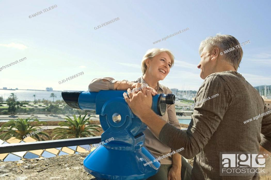 Stock Photo: Man and woman leaning on coin-operated binoculars.