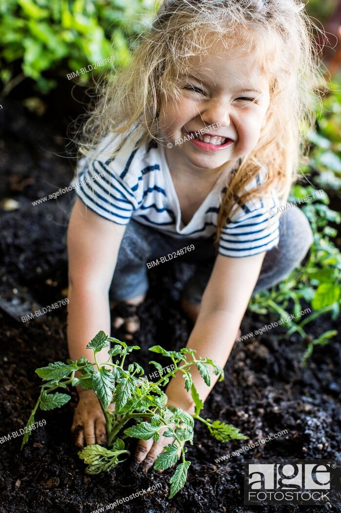 Stock Photo: Caucasian girl posing with plant in garden.